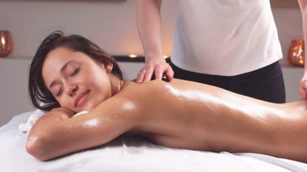 Okouzlující krásná dívka tráví čas ve wellness beauty spa centru, ležící na bílých prostěradlech