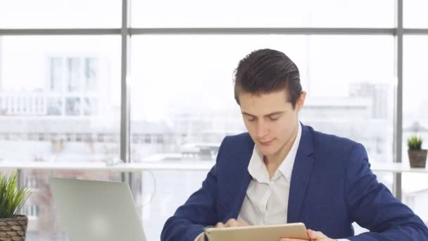 Young businessman sitting by table with laptop and looking in camera.