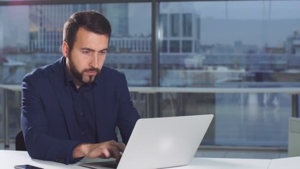 Portrait of modern attractive businessman working at desk in office using laptop