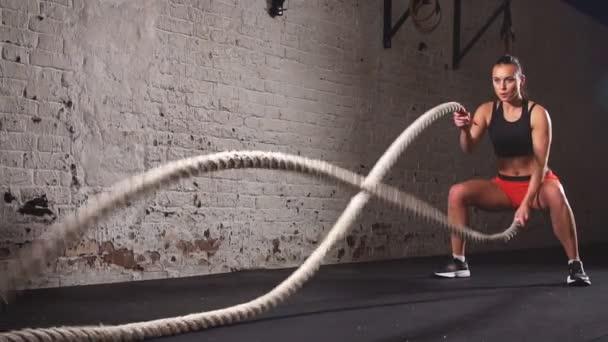 Sportovní žena cvičení s bojovými provazy v rámci svého fitness tělocvična cvičení.