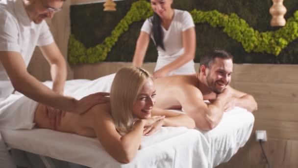 Video profesionálních mladých masérů provádějících aromaterapeutickou masáž esenciálním olejem příjemným klientům ležícím na masážním stole