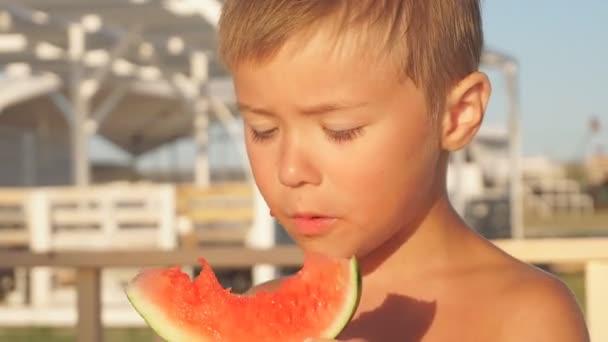 Junge isst Wassermelone auf dem Meer