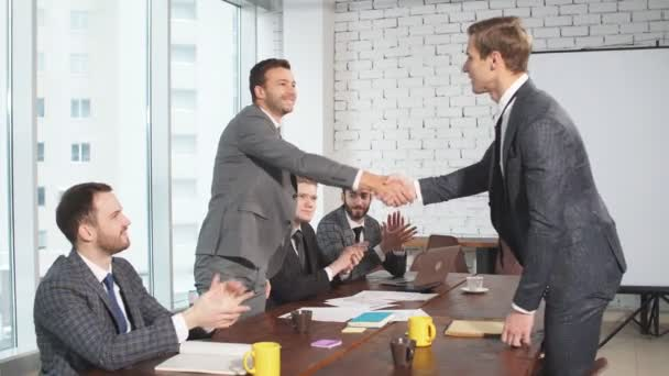 Young business partners shaking hands