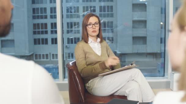 Női professzionális pszichológus beszél, hallgat és jegyzetel a jegyzetfüzetben.