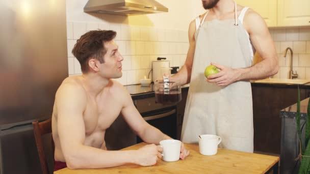 Fiatal szerető férfi boldog pihenés ital kávé ül a konyhában a reggeli koncepció.