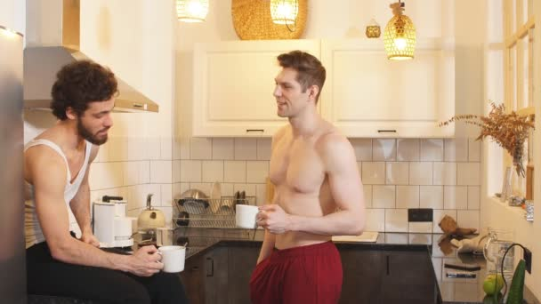 Two young sexy guys in the kitchen. Love and relationships.