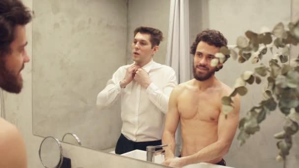 Fiatal sportoló meleg pár a tükör előtt reggel a fürdőszobában