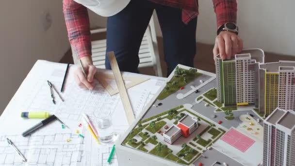 Mladí odborníci architekti vytvářejí vysoce postavený model budovy.