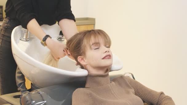 Profesionální kadeřník v salonu krásy s klienty