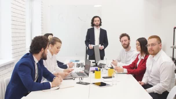Mladá skupina programátorů pracuje na novém projektu. Skupina kolegů pracuje s papírovými dokumenty a finančními zprávami