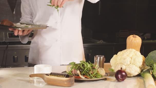 Egy közeli kéz a séf kísérő saláta sajt rozmaringgal, só. Finom, modern konyha, exkluzív recept