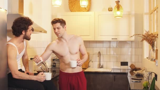 Pár meleg, jóképű férfi, akik kávézgatnak a konyhában reggel..