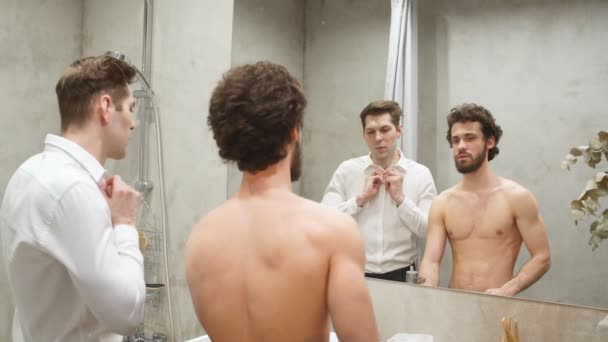 Fiatal sportoló meleg pár a tükör előtt reggel a fürdőszobában.