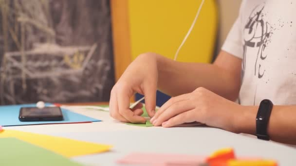 Close-up of teenagers hands working with paper in creative Studio, Child performs origami