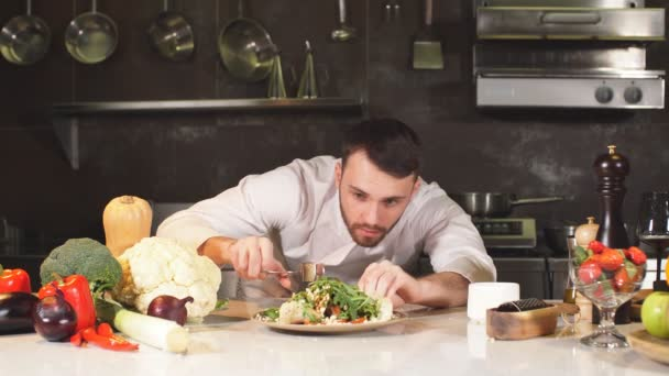 A fiatal séf zöldséggel díszíti a különleges ételét. Egy modern konyhában dolgozik.