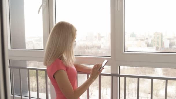 Depressed dívka v ochranné masce pomocí smartphone během self-izolace doma.
