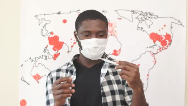 Young American guy measures the temperature with a mercury degree. Man feels deteriorating health at home quarantine