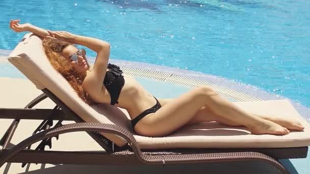 Hezká mladá žena relaxaci u bazénu na palubě židle při pohledu na krásný hotel.