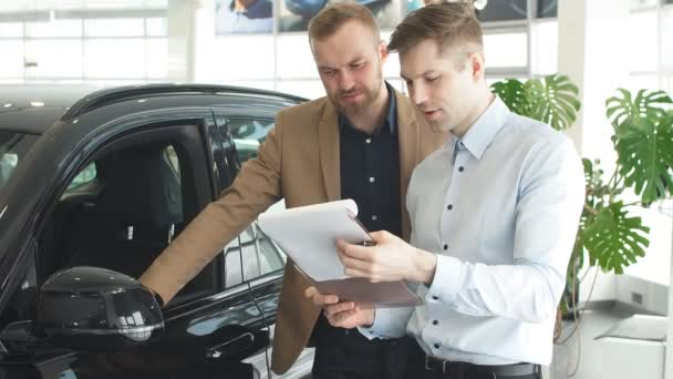 Affable handsome consultant and client in dealership