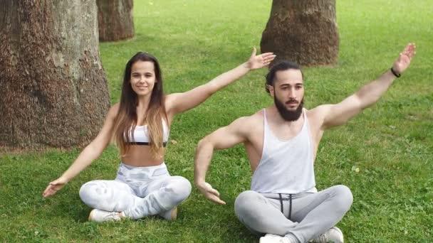 Fiatal pár jóga gyakorlatokat végez.