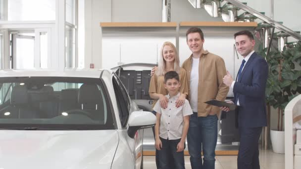 Happy caucasian family now the owners of new beautiful car.