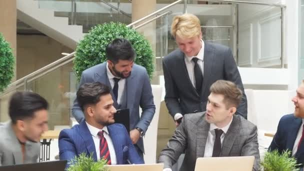 European and arabic young businessmen sit communicating, look at each other, have conversation about new deal.