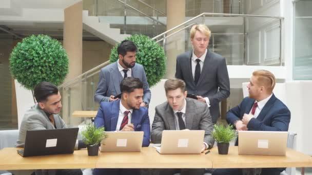 Gruppe multinationaler junger Männer blickt auf Laptop, während sie über neues Projekt, neuen Deal diskutieren.