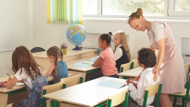 Fiatal lány tanár segít a fiatal diákok egy írás leckét