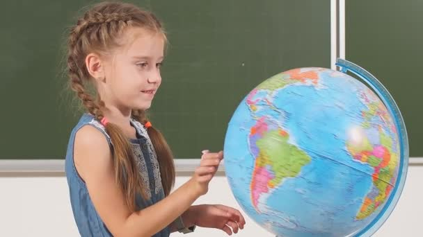 Young school girl with a globe in classroom chalkboard on background