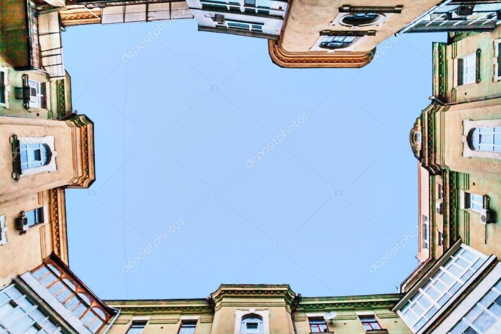 view from the bottom up at the sky, tall old houses, wells, balc