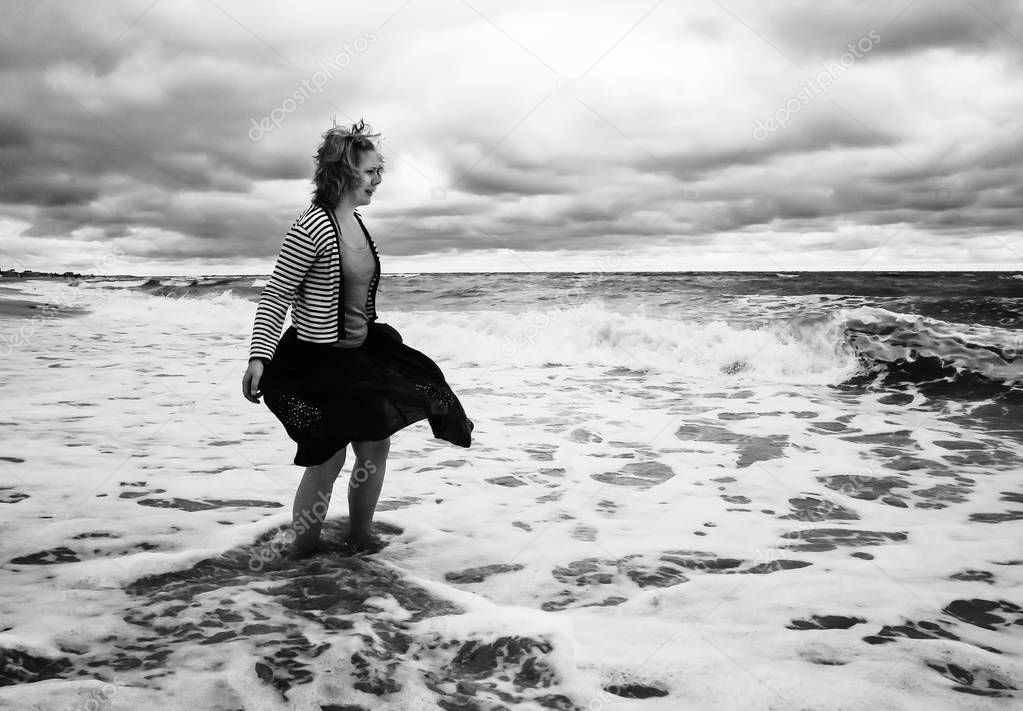 A young woman in a billowing skirt stands among the stormy sea w