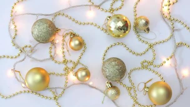 Vánoční zlatý dekor na bílém pozadí a blikající věnec posypaný hvězdami. Pohled shora. Opraveno. Koncepce, Vánoce a Nový rok oslavy.