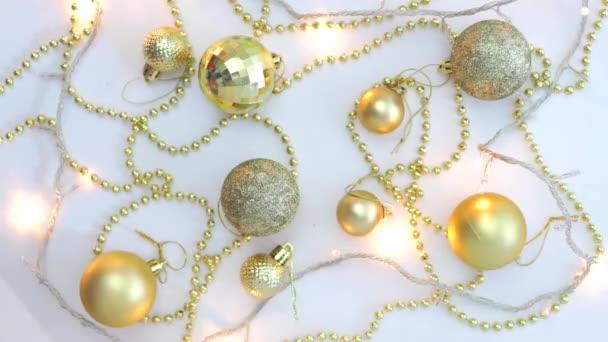 Vánoční zlatý dekor na bílém pozadí a věnec blikající rozmazanými světly. Pohled shora. Opraveno. Koncepce, Vánoce a Nový rok oslavy.