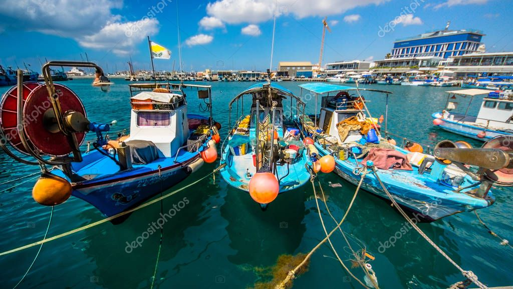 The old fishing boats are waving on the waves. Shipyard  in Limassol, Cyprus,  august 2017