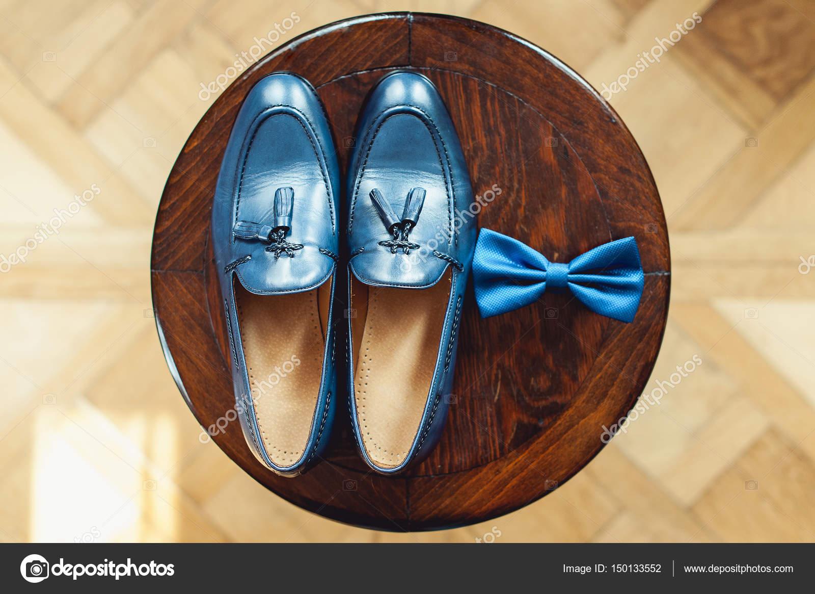 Scarpe blu e papillon su uno sgabello rotondo in legno accessorio
