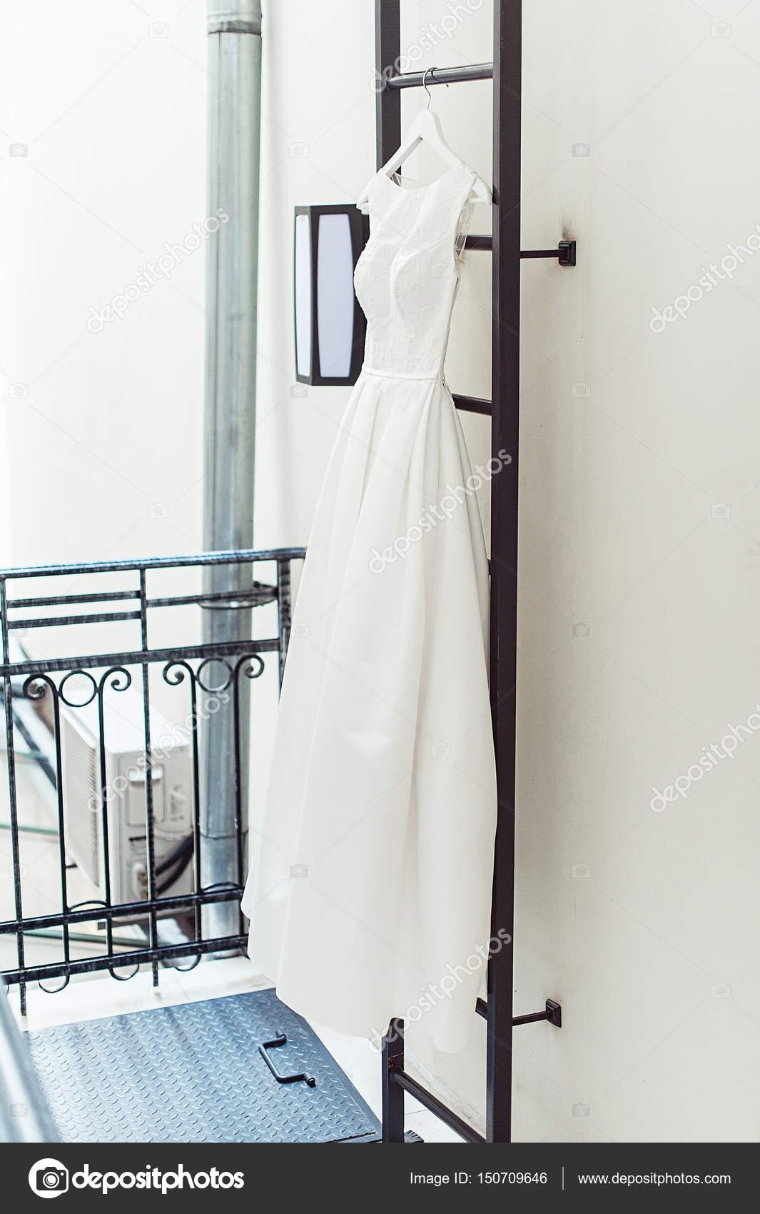 d07455ae0448 Πανέμορφο λευκό νυφικό σε μια φωτιά σκάλα στο μπαλκόνι. Αξεσουάρ νύφες την  ημέρα του γάμου