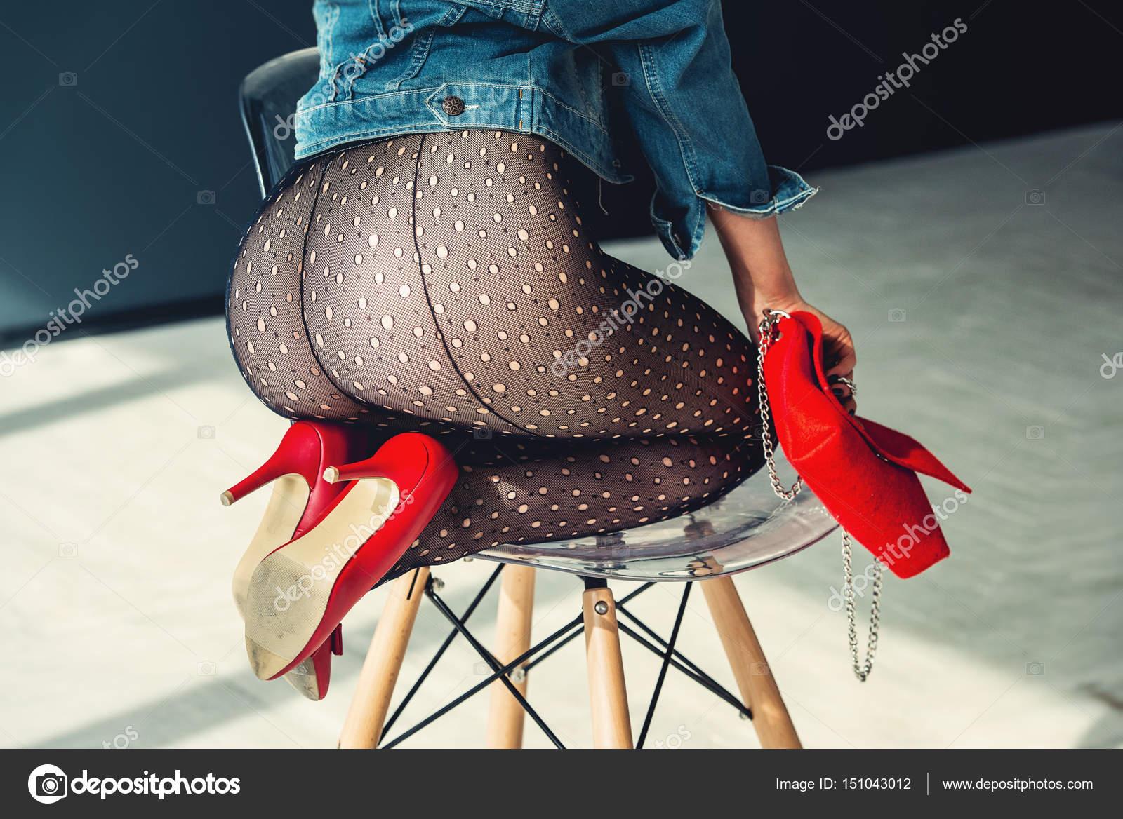 Magnifique fille vêtue d\u0027une chaussures à talons hauts bleu jeance veste,  rouge avec rouge petit sac et collants transparents sans culotte. posant  assis sur