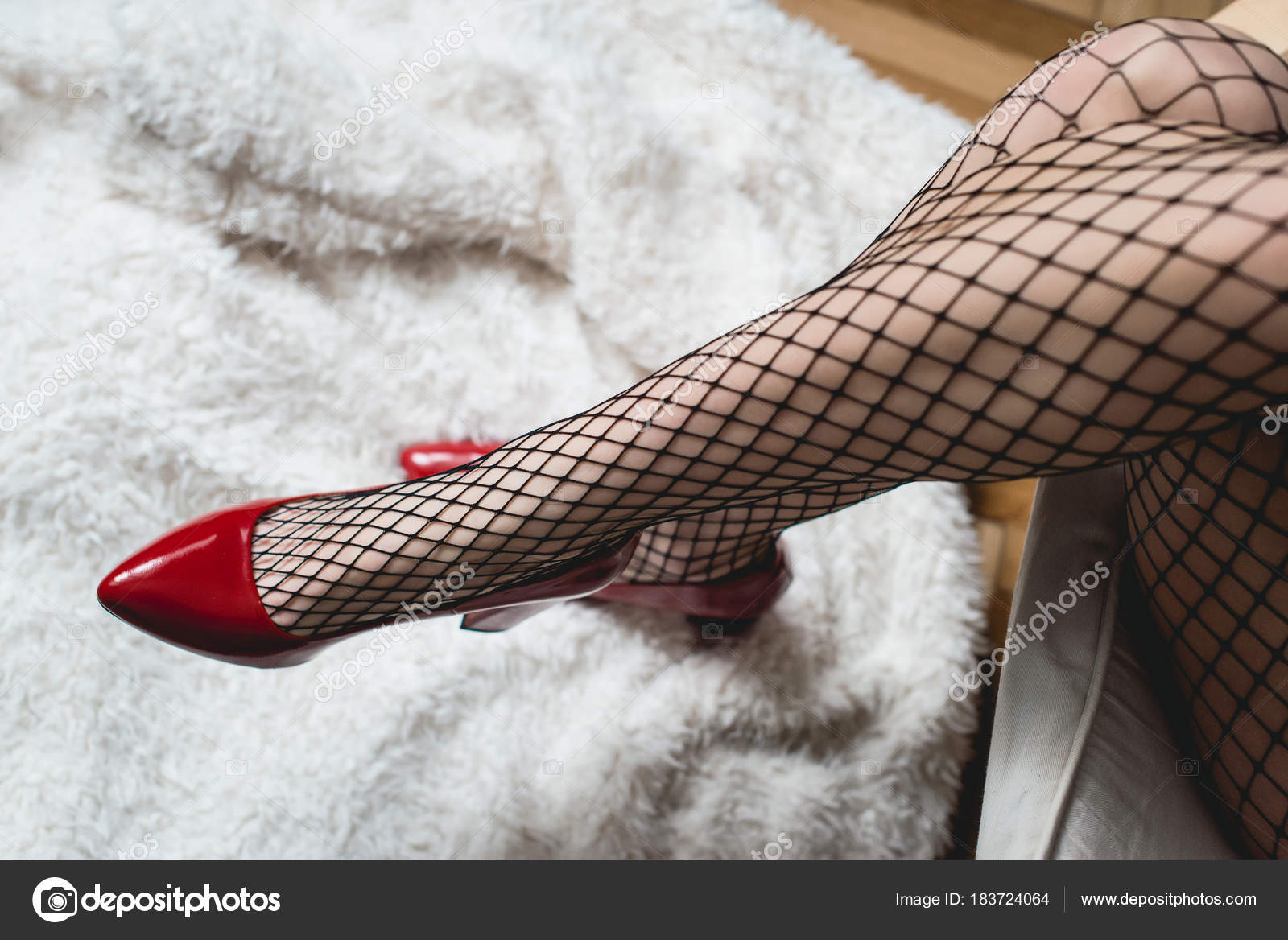 1ef4121fa5f Sexy female legs in high heel red shoes and fishnet stockings. Retro ...