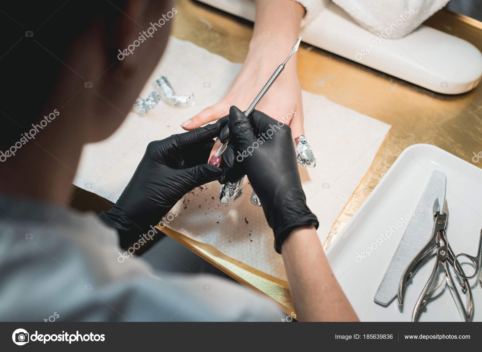 Primer plano de un manicurista quitar viejo esmalte de uñas con ...