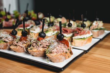 tasty pinchos with tuna, chorizos, salmon, egg, dried tomatoes, avocado, salmon, bacon, Hamon, Brie Cheese, Olives and Pesto Sauce, traditional spanish snack