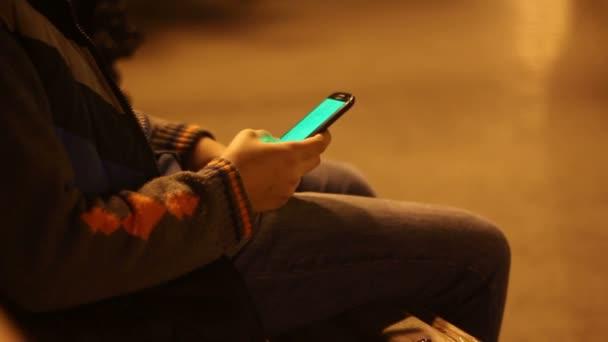 Fiatal fiú a smartphone-ban éjszaka egy nagyvárosi parkban