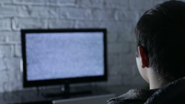 Kisfiú nézte az lcd TV-vel, egy sötét szobában loft stílusú téglafalak, hátsó nézet.