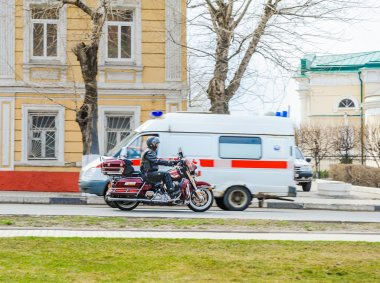 The motorcyclist and ambulance car on the street October revolution in Kolomna