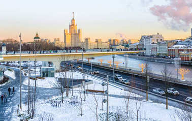 MOSCOW, RUSSIA - January 9, 2018: Park Zaryadye in the winter. The view of the fragment of the unique floating bridge and Stalin skyscraper on the Kotelnicheskaya embankment at sunset in winter