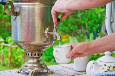 Mistress pours hot water from wood burning samovar into the Cup outdoor