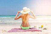 Dokonalý ráj letní prázdninové štěstí bezstarostné šťastná žena relaxační posezení v písku se těší tropickou pláž destinace. Zadní pohled na bikiny dívka drží růžové slaměný klobouk na Karibské dovolené