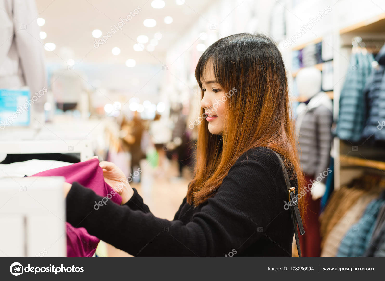 c12858f98bb Half body shot of a happy asian young woman with shoulder bag looking at  clothes hanging on the rail inside the clothing shop.