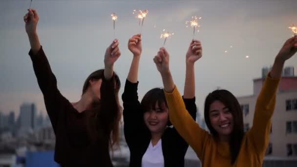 Colpo esterno dei giovani alla festa sul tetto. Gruppo felice di asia ragazza amici godere e giocare sparkler a tetto top party al tramonto di sera. Festa celebrazione festiva. Festa adolescente lifestyle.
