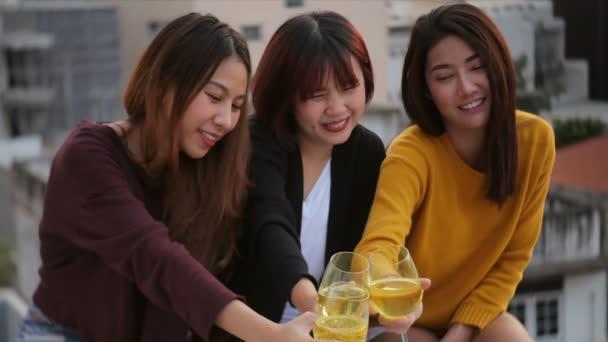 A kültéri lövés a fiatal emberek pirítás ital egy tetőtéri partin. Fiatal ázsiai lány barátok lógni italok. Ünnepi ünnep ünnepi buliba. Tizenéves életmód fél. Szabadság és a szórakoztató szabadtéri.
