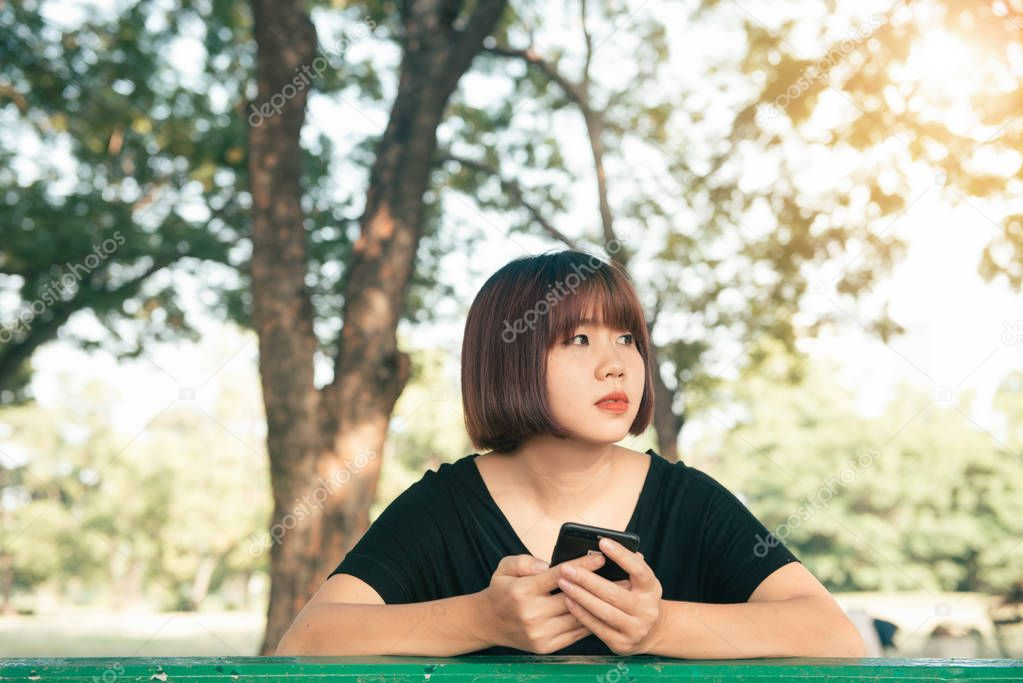 Cute asian woman reading pleasant text message on mobile phone while sitting in park spring day. Asian woman using on smart phone with feeling relax and smiley face. Lifestyle and technology concepts.